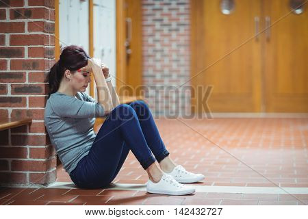 Stressed mature student sitting in locker room at college