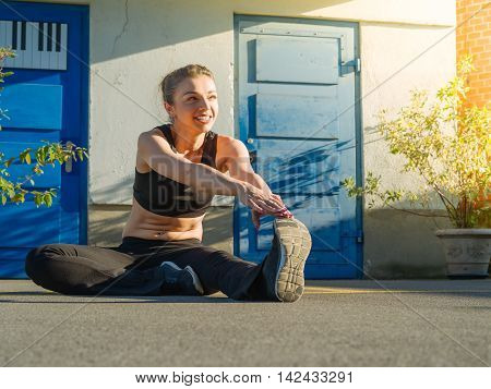 Photo of a toned young woman stretching her leg outside before a run late in the day.
