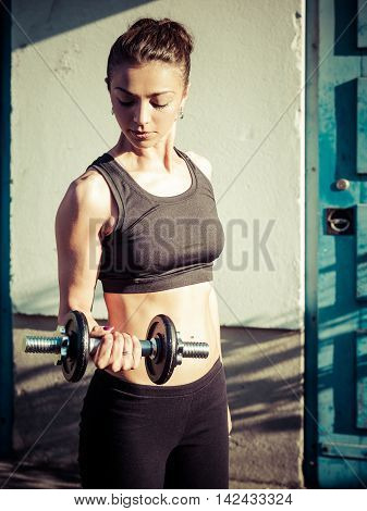 Photo of a toned young woman exercising with a dumbbells outside. Filtered for different look.