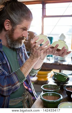 Male potter checking bowl in pottery workshop