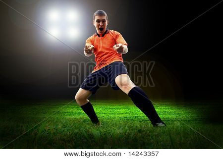 Happiness football player after goal on the field of stadium with light
