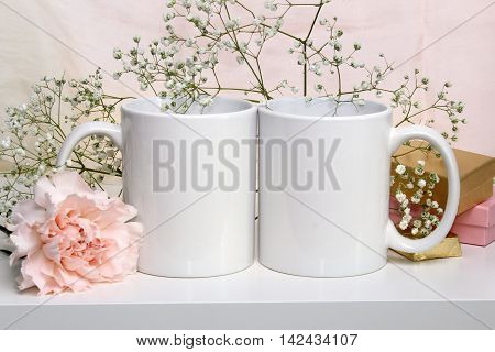 Two white mugs cups wedding mockup. Gypsophila carnation gifts on the background. Pastel colors