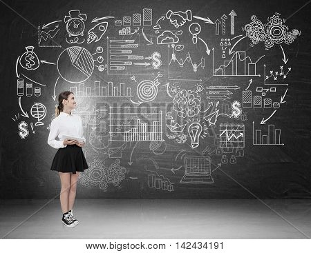 Woman in black skirt standing against blackboard background holding tablet. Sketches pictured on board. Concept of studying.