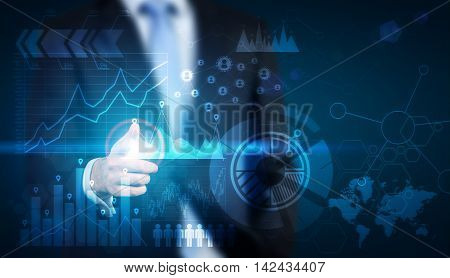 Businessman in suit touching futuristic display with graphs and sketches on it. Concept of future is now.  Toned image. Double exposure.