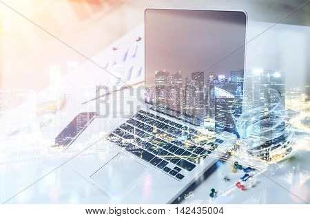 Laptop and smart phone on desk. Big city in background. Concept of corporate work. Toned image. Double exposure