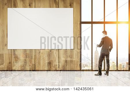 Businessman standing near large window in big city office. Horizontal poster on wooden wall. Double exposure of city. Concept of CEO work. 3d rendering. Mock up. Toned image