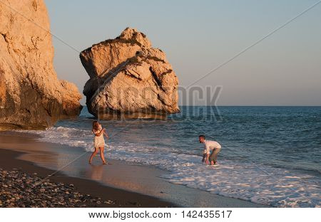 Paphos Cyprus - July 7 2016: Young lovely and happy couple playing with water at the Aphrodite birth place beach at Paphos in Cyprus