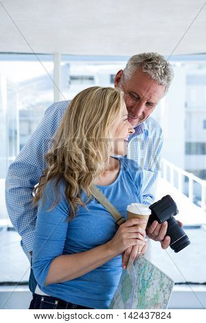 Mature couple holding camera and coffee cup at home