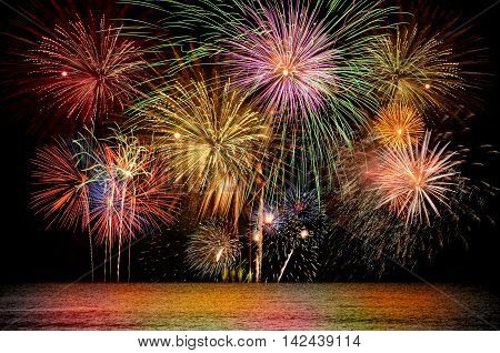 Colorful firework celebration on dark night sky background. Beautiful fireworks show on clear night sky.