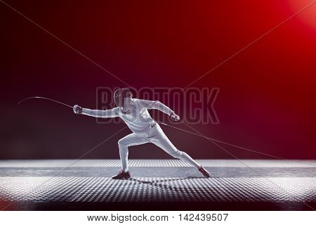 Fencing player isolated on the black red gradient background