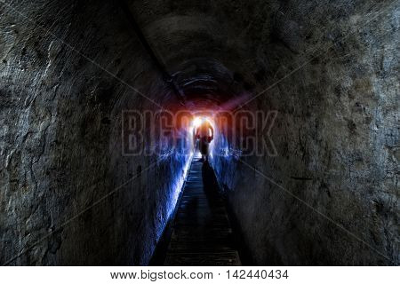 Old dark endless tunnel in the mountains with dramatic high contrast illumination and figure appearing from the light