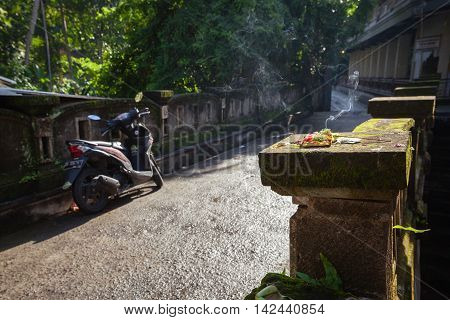 Burning offerings on the old mossy bridge in the morning hour Ubud Bali Indonesia.