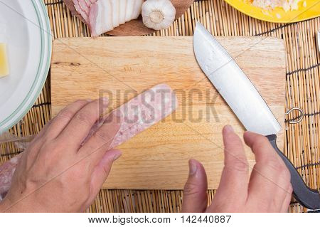 Chef cutting bacon with knife before cooking / cooking spaghetti concept