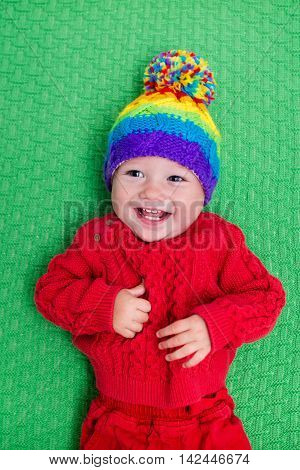 Cute baby in warm wool knitted hat on a red blanket. Autumn and winter clothing for young kids. Colorful knitwear for children. Adorable little boy ready for a walk on a cold fall day.