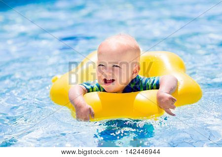 Happy little baby playing with colorful inflatable ring in outdoor swimming pool on hot summer day. Kids learn to swim. Children wearing sun protection rash guard relaxing in tropical resort