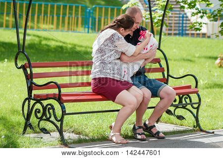 Young Family Sitting On A Park Bench. Father Holding Newborn Daughter In Her Arms.
