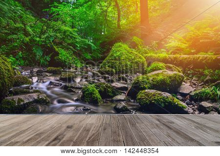 Forest stream running over mossy rocks with wooden walkway. Vintage tone