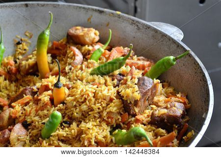 Large pot with Uzbek pilaf with tomatoes and green chilli peppers