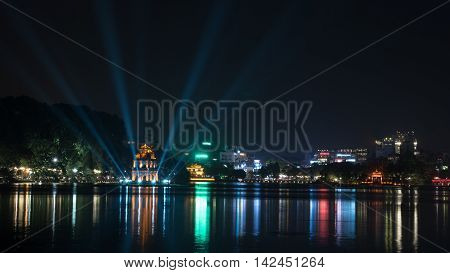 Hanoi view at night with illuminated Turtle Tower and Hoan Kiem Lake in city centre. Colorful lights reflecting in dark water