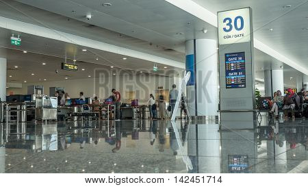 HANOI, VIETNAM - OCTOBER 27, 2015: Low angle shot of airport hall with gate information and people in security checkpoint. Noi Bai International Airport, the biggest one in northern Vietnam