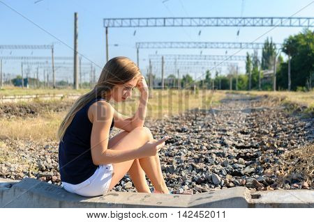 Girl teenager in top and shorts using cellphone while sitting on concrete of unfinished rail track in the countryside