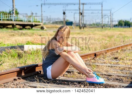 Lonely and sad teenager girl sitting on rusty rail track in the countryside. Adolescence problems