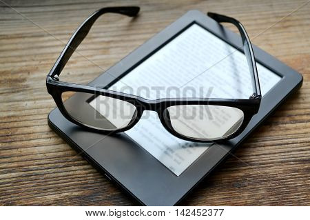 Black ereader with retro glasses on wooden table
