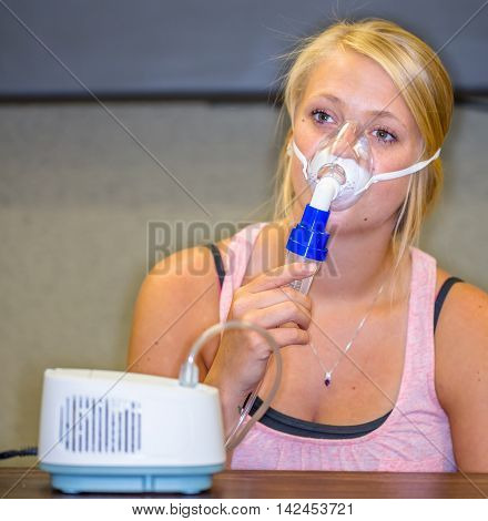 A young woman using a nebulizer aerosol mask and compressor.