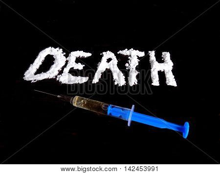 Cocaine drug powder in shaped death word and injection on black background