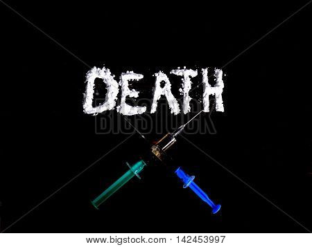 Cocaine drug powder in shaped death word and two crossed injections on black background