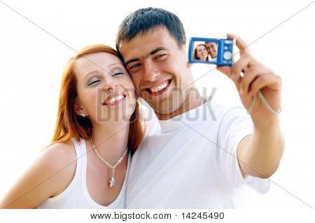 Una atractiva pareja Junta en el fondo blanco, tomando un autorretrato.