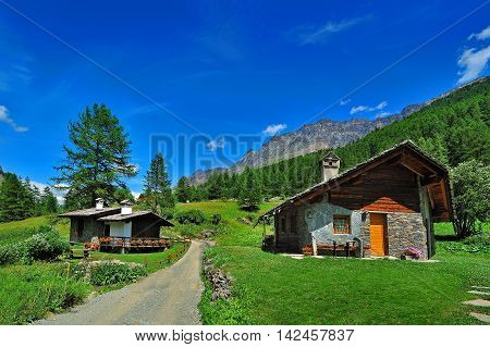 Alpien houses in Rhemes Notre Dame with mountains background