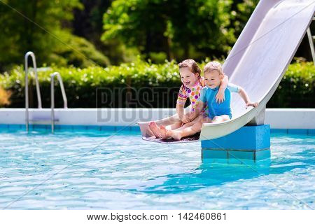 Happy little boy and girl play on water slide in outdoor swimming pool on hot summer day. Kids learn to swim. Children wearing sun protection rash guard sliding on aqua playground in tropical resort