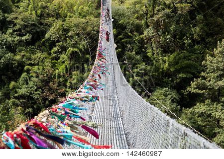 Ghasa, Nepal - November 05, 2014: Local people crossing a suspension bridge on the Annapurna Circuit