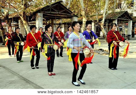 Wan Jia China - October 29 2012: A women's waist drum band with red and yellow silk scarves rehearsing a routine in the town's market square