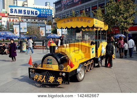 Chengdu China - November 28 2007: A bright yellow tourist train offers rides to tourists along pedestrians-only Chun Xi Street