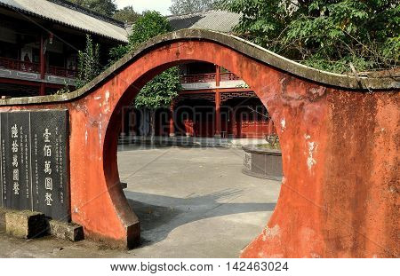Dan Jing Shan China - November 16 2012: A rounded moongate doorway leads from the central courtyard to the monks' dormitories at the Fo Shan Gu Xi Buddhist Temple