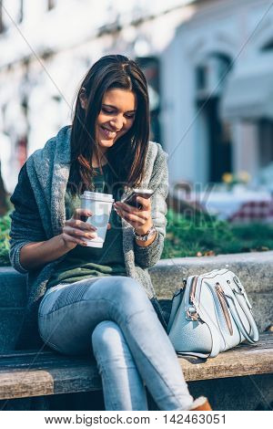 Teenager With Take-away Coffee Using Phone
