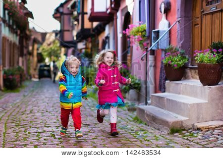 Cute little girl and boy walking down a street in historical medieval city center on cold autumn day. Children during fall vacation in Eguisheim Alsace France. Travelling and tourism with kids.