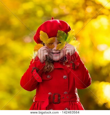 Happy little girl in red beret and trench coat playing in beautiful autumn park on warm sunny fall day. Kids play with golden maple leaves.