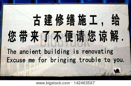 Beijing China - May 2 2005: Amusing sign in both Chinese and English explains in fractured English that a Forbidden City building is closed for renovations