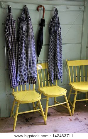 Three yellow chairs in wood paneled room, with clothing and umbrella  hanging over them