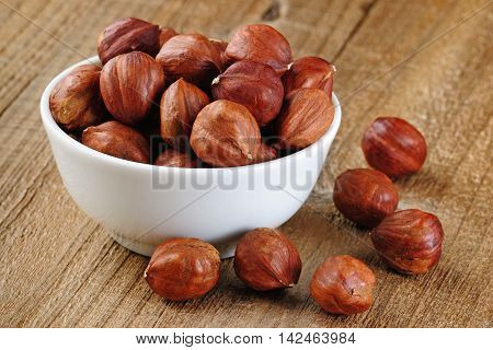 Pile of hazelnuts in bowl on wooden background