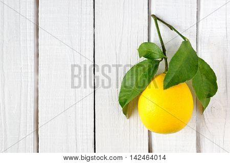 Lemon with leaves on white wooden background