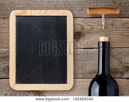 Wine bottle and blank chalkboard on wooden background