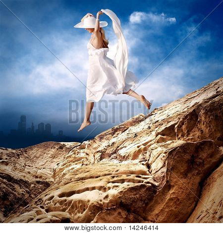 Beautiful girl in White on the mauntain under sky with clouds