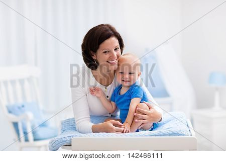 Young mother taking care of little boy in white sunny nursery with changing table baby crib and rocking chair. Diaper change and clothing. Mom and son in beautiful bedroom at home.