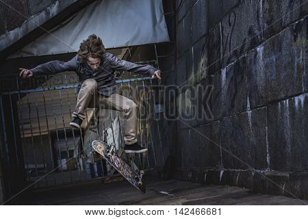 Young skateboarder performing a skateboard trick against graffiti wall