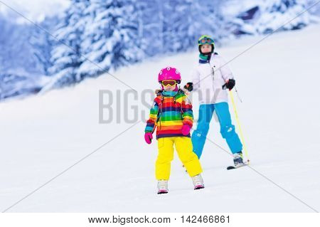 Boy and girl skiing in mountains. Toddler kid and teenager with helmet goggles poles. Ski race for children. Winter sport for family. Kids ski lesson in alpine school. Little skier racing in snow