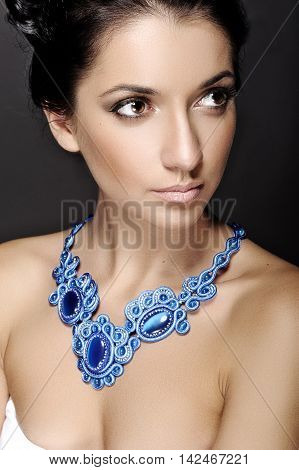 portrait of brunette girl with blue costume jewelery close up
